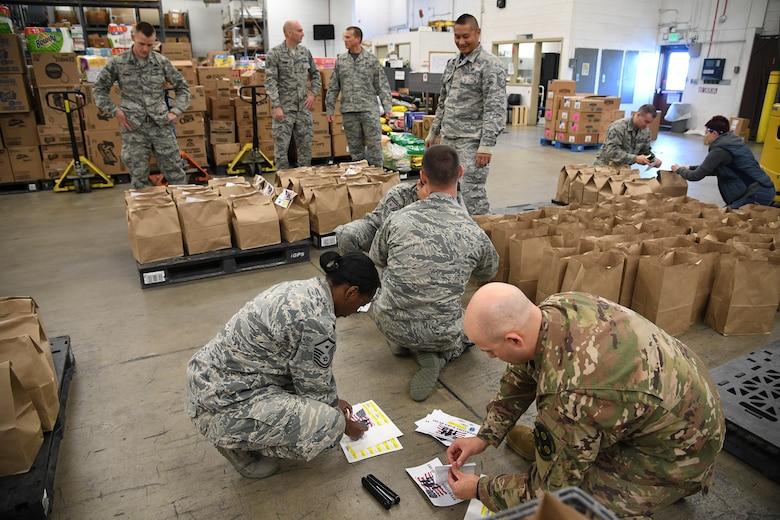 Members of Hill's First Sergeant Council pack Operation Warm Heart Thanksgiving bags on Nov. 2, 2018, at Hill Air Force Base, Utah. The bags of sides dishes along with a turkey and a pie donated by commissary vendors will be delivered to selected Airmen to assist with the upcoming holiday. (U.S. Air Force photo by R. Nial Bradshaw)