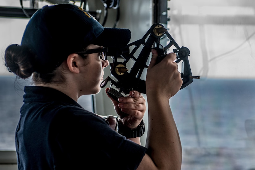 A seaman recruit  uses a stadimeter sextant looking across sea.