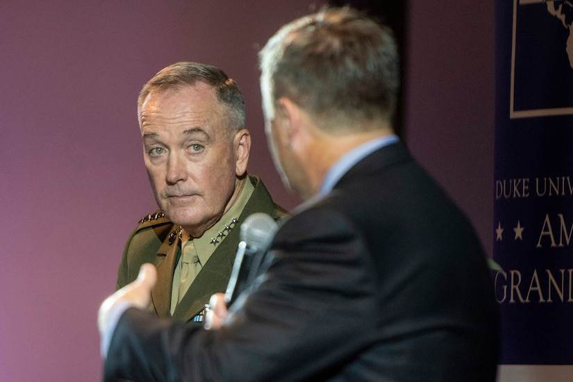 Marine Corps Gen. Joe Dunford listens as another man speaks to him.