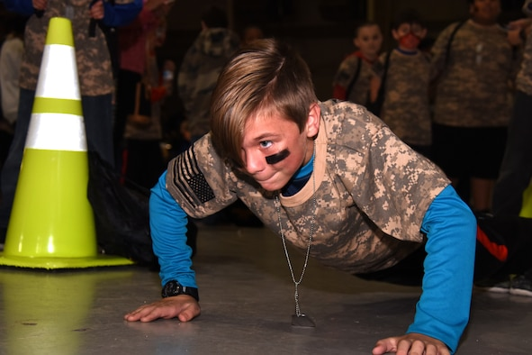 Scott, an Operation KIDS participant competes in a push-up competition while waiting for the processing of the rest of his group at the Louis F. Garland Department of Defense Fire Academy Goodfellow Air Force Base, Texas, Nov. 3, 2018. Drill instructors showed groups different parts of being in the military, including pushups, proper formation techniques and facing movements. (U.S. Air Force photo by Airman 1st Class Seraiah Hines/Released)