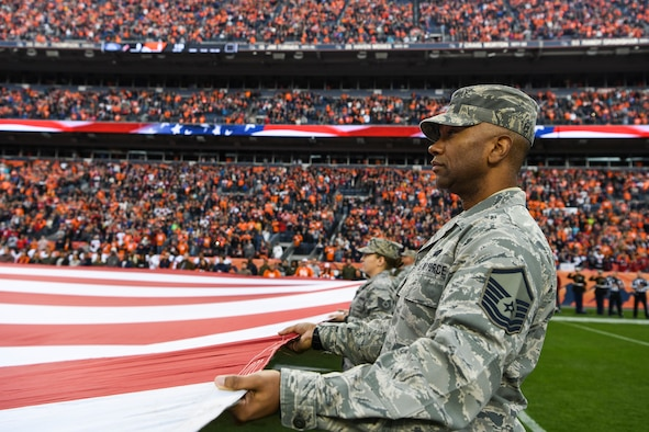 Master Sgt. Malcolm Chandler, 140th Operations Group commander support staff, holds the American flag during the national anthem Nov. 4, 2018, at Mile High Stadium in Denver. Salute to Service is a year-round effort to honor, empower and connect the nation's service members, veterans and their families. (U.S. Air Force photo by Airman 1st Class Jake Deatherage)
