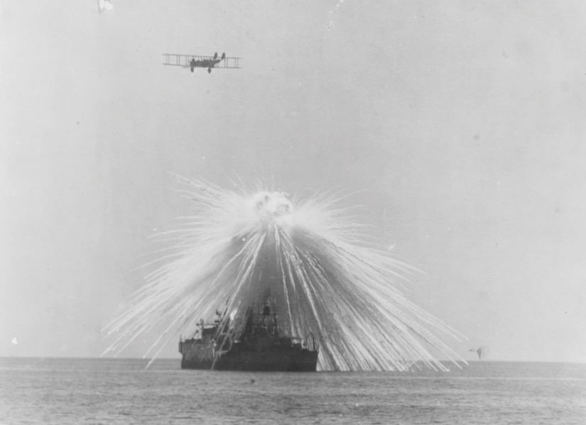 Ex–USS Alabama hit by white phosphorus bomb dropped by NBS-1 in bombing tests, as Army Martin twin-engine bomber flies overhead, Chesapeake Bay, September 23, 1921 (U.S. Naval History and Heritage Command)