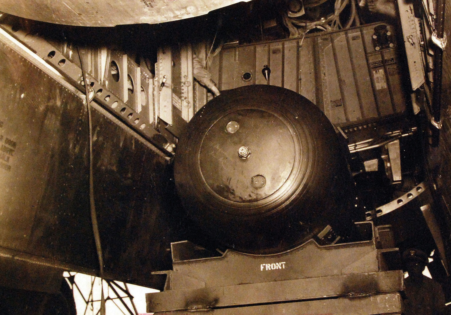 """Atomic bomb """"Little Boy"""" hoisted into bomb bay of B-29 Superfortress, Enola Gay, Tinian Island, August 1945 (U.S. Navy National Museum)"""