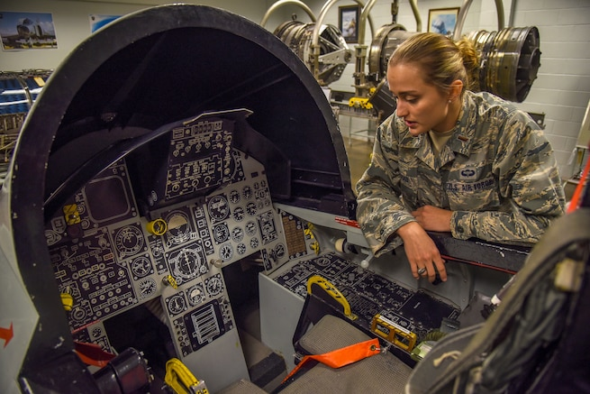 2nd Lt. Yelizaveta Patenko, a student in the Aircraft Maintenance Officer Course, explains the egress system in an F-15 Strike Eagle model at Sheppard Air Force Base, Texas, Oct. 31, 2018. The emergency equipment must be continuously checked and rechecked in order to maintain the safety of the operators when they take to the skies. (U.S. Air Force photo 2nd Lt. Megan Morrissey)