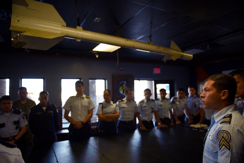 Distinguished cadets from different Latin American Air Force academies gather in the heritage room of the 309th Fighter Squadron to listen to U.S. fighter pilots speak about their experiences Oct. 31, 2018, at Luke Air Force Base, Ariz. Luke was one of several base visits the cadets made on their cross-country tour, a part of the Department of Defense Latin American Cadet Initiative. (U.S. Air Force photo by Senior Airman Ridge Shan)