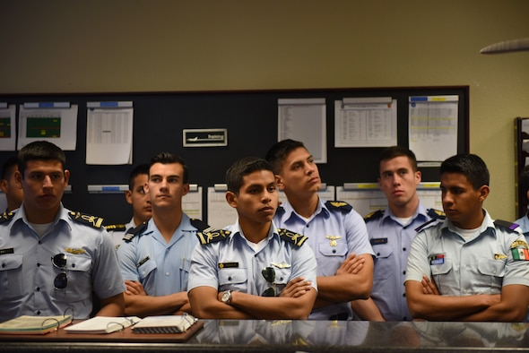 Distinguished cadets from different Latin American Air Force academies listen to U.S. fighter pilots speak about mission procedure at the 309th Fighter Squadron operations desk Oct. 31, 2018, at Luke Air Force Base, Ariz. The group was composed of the top two cadets from each of various Latin American air service academies from countries including Mexico, Brazil, and Colombia. (U.S. Air Force photo by Senior Airman Ridge Shan)