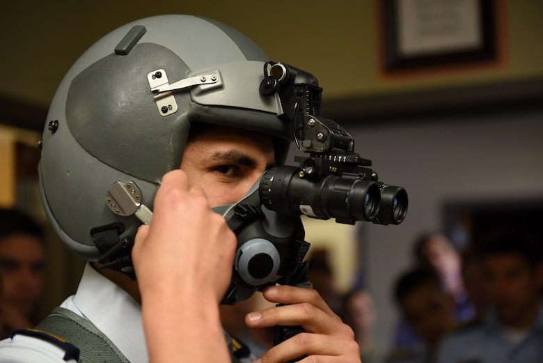 A cadet from a Latin American air service academy tries on an F-16 fighter pilot's helmet with night vision goggles Oct. 31, 2018, at Luke Air Force Base, Ariz. Cadets from air service academies across South America visited Luke as part of the Department of Defense Latin American Cadet Initiative. (U.S. Air Force photo by Senior Airman Ridge Shan)