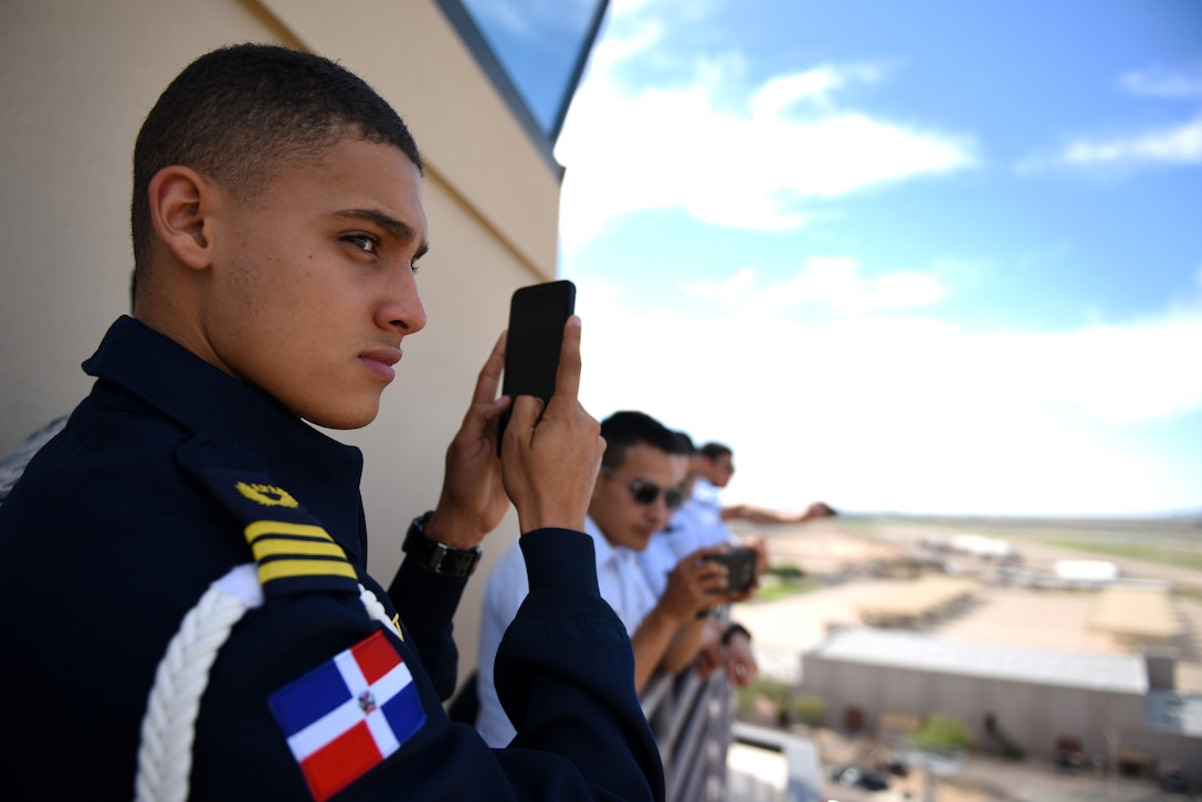 Gean Louis Torres Herrera, Dominican Air Force cadet and class leader, takes photos of the view from the balcony of the air traffic control tower Oct. 31, 2018, at Luke Air Force Base, Ariz. Torres Herrera is one of a group of the top two cadets from each of various Latin American air service academies from countries including Mexico, Brazil, and Colombia, who are touring U.S. bases as a part of the Department of Defense Latin American Cadet Initiative. (U.S. Air Force photo by Senior Airman Ridge Shan)