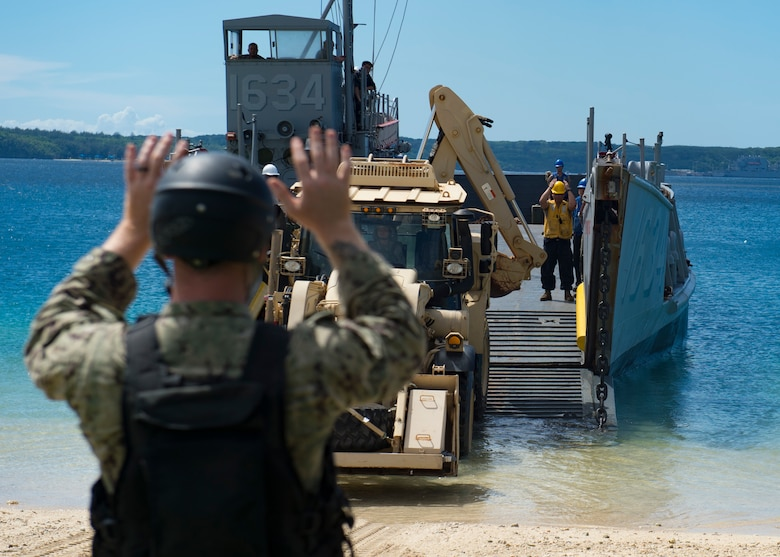 SANTA RITA, Guam (Nov. 06, 2018) Sailors assigned to Landing Craft Utility (LCU) 1634, attached to Naval Beach Unit (NBU) 7 forward-deployed to Sasebo, Japan, embarked aboard amphibious dock landing ship USS Ashland (LSD 48), direct a Solider assigned to the Guam Army National Guard as she drives to pick up supplies for Super Typhoon Yutu recovery effort. Service Members from Joint Region Marianas and U.S. Indo-Pacific Commands are providing Department of Defense support to the Commonwealth of the Northern Mariana Islands civil and local officials as part of the FEMA-supported Super Typhoon Yutu recovery effort.