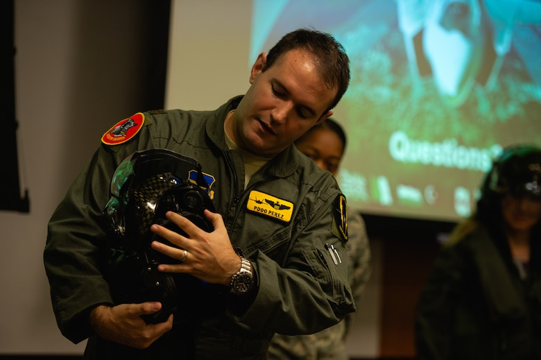 Maj. Fernando Perez, 61st Fighter Squadron, director of weapons, briefs members of the Personalized Learning Cohort about an F-35A Lightning II helmet during a visit to Luke Air Force Base, Ariz., Nov. 2, 2018. Throughout the tour, members of the cohort were given the opportunity to speak with Airmen and receive a comprehensive review of some of the resources and tools used to train fighter pilots. (U.S. Air Force photo by Senior Airman Alexander Cook)