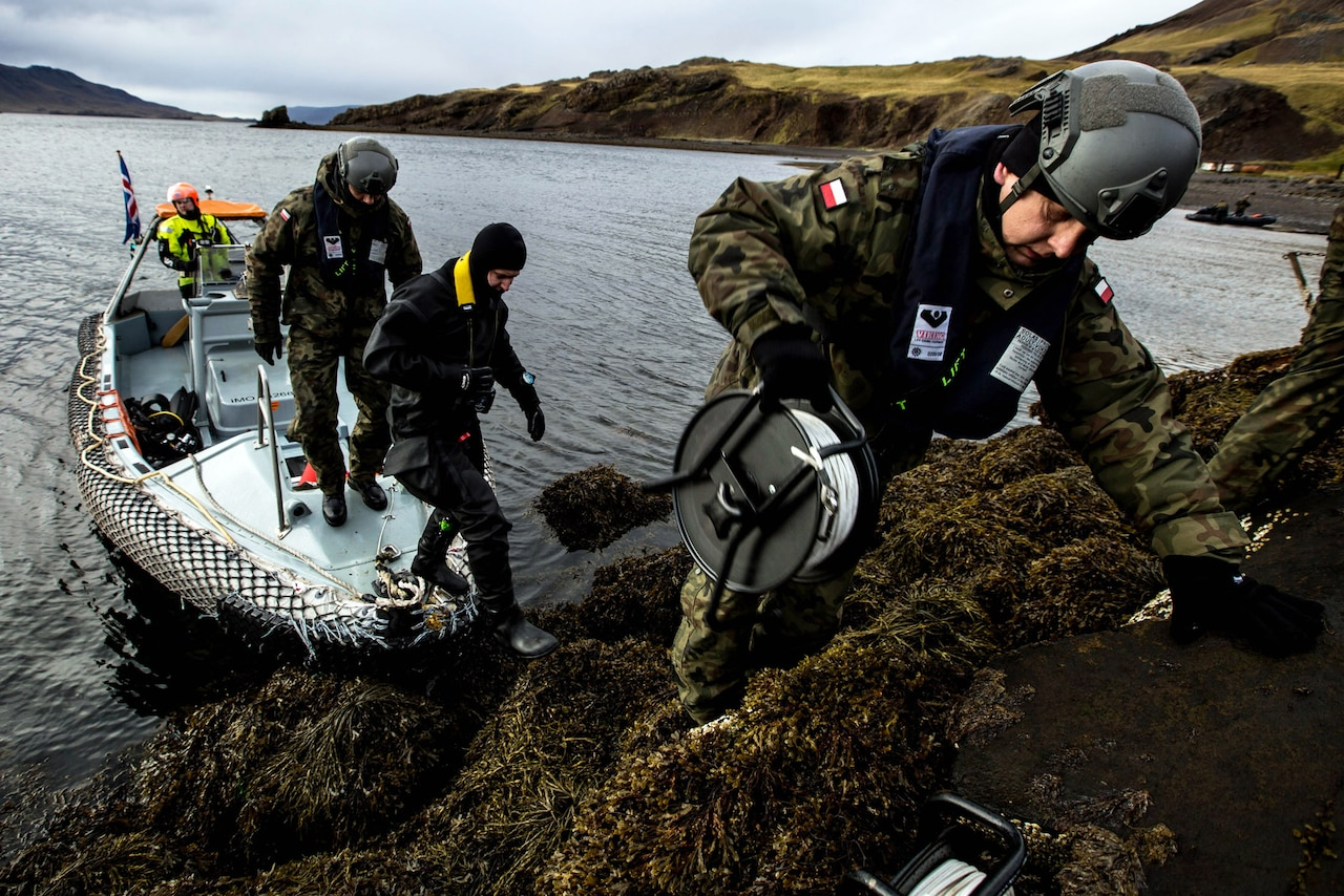 Three specialists come ashore from boat.