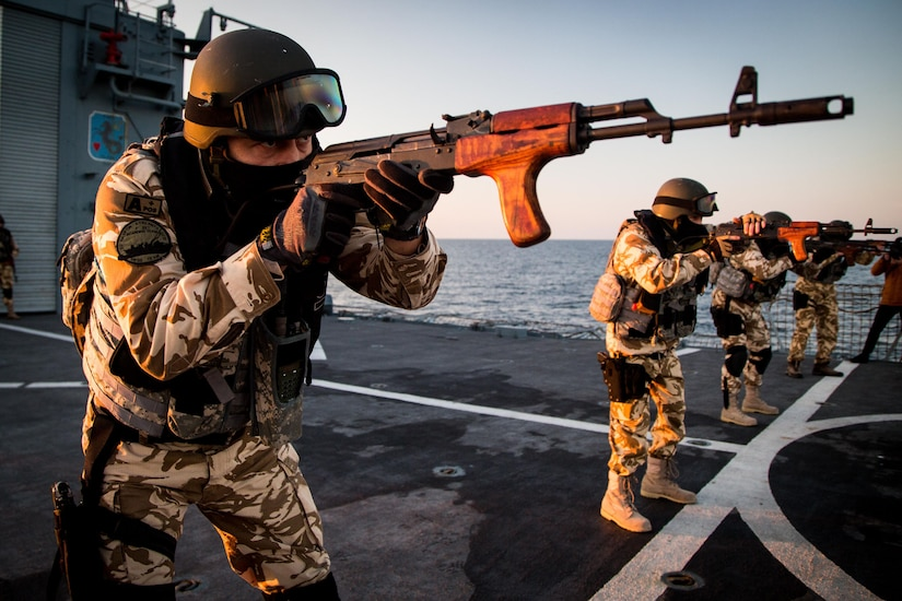 Romanian navy member points weapon during drill