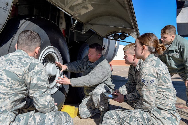 Staff Sgt. Joseph Martinez, center, a C-130 crew chief apprentice course instructor in the 362nd Training Squadron, talks about the wheel assembly of a MC-130P Combat Shadow during training at Sheppard Air Force Base, Texas, Nov. 5, 2018. The squadron received the MC-130P, the newest ground instructional training aircraft in the inventory, in October from the California Air National Guard. This variation provides updated components such as the carbon fiber-style braking system that replaced the obsolete multi-disc system on older C-130s. (U.S. Air Force photo by John Ingle)