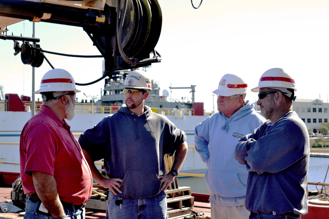 photo of members of the U.S. Army Corps of Engineers take part in an on-camera interview on the deck of the derrick boat Elizabeth