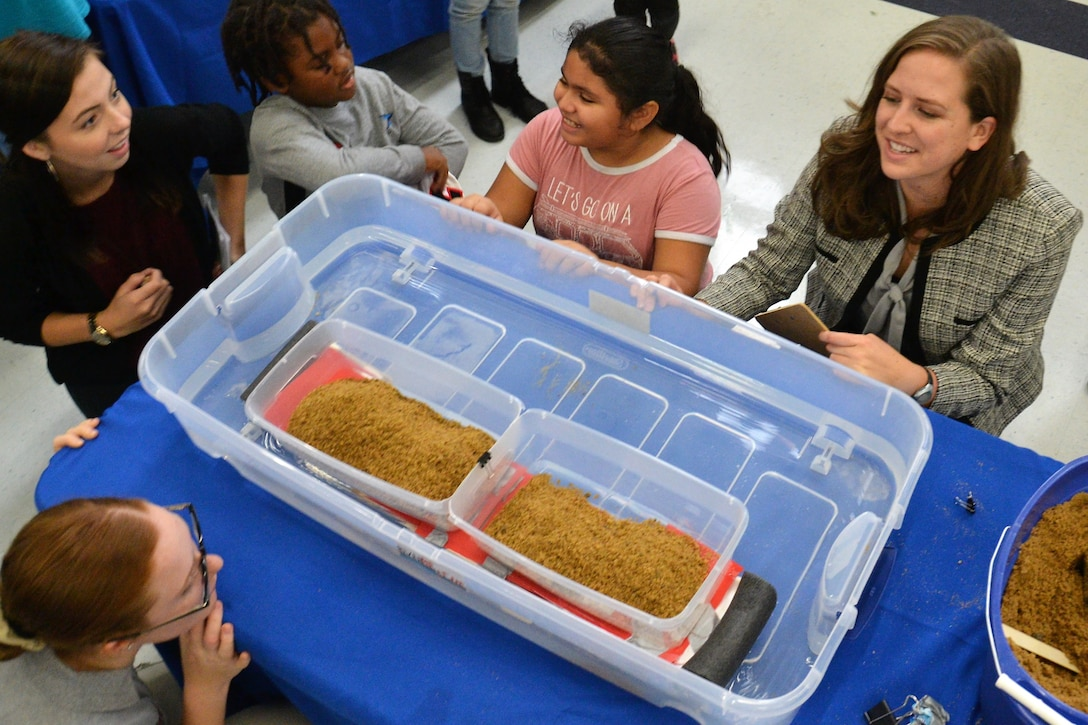 Adults and children are gathered around a container filed with water to see how much sand the model of a floating bridge can handle before it touched the bottom