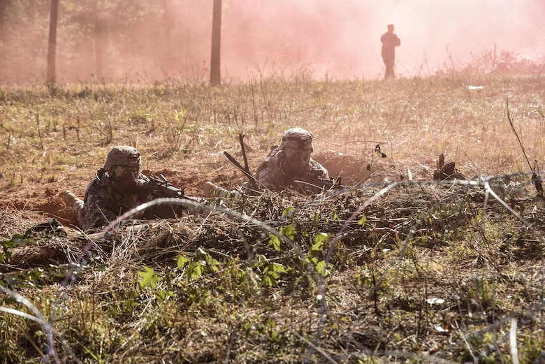 U.S. Army Soldiers assigned to the 331st Transportation Company, 11th Trans, Battalion, 7th Trans. Brigade (Expeditionary), take cover during a gas attack during Area Defense training at Fort Pickett, Virginia, Oct. 29, 2018.
