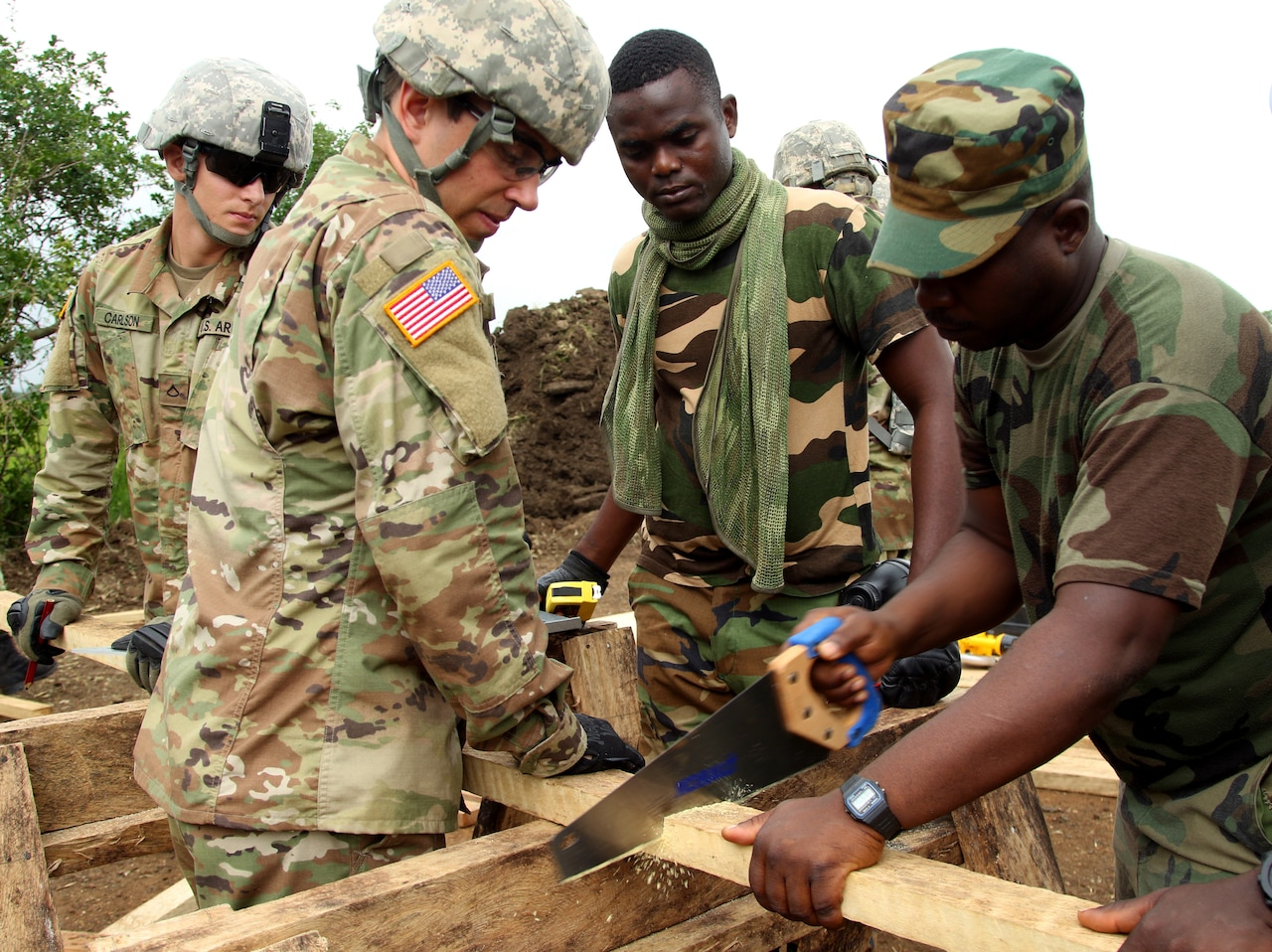 Guardsmen and Ghanaian troops gather to saw wood.