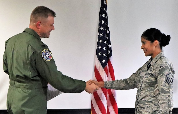 Col. Allen Duckworth, commander of the 340th Flying Training Group, JBSA-Randolph, Texas congratulates to Master Sgt. Jennifer Robles on her reenlistment. U.S. Air Force photo by Janis El Shabazz