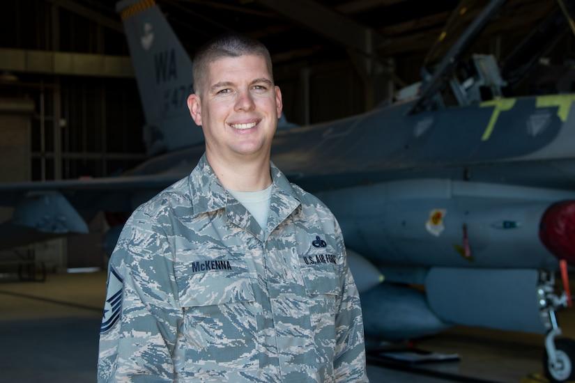 An airman stands in a hangar.