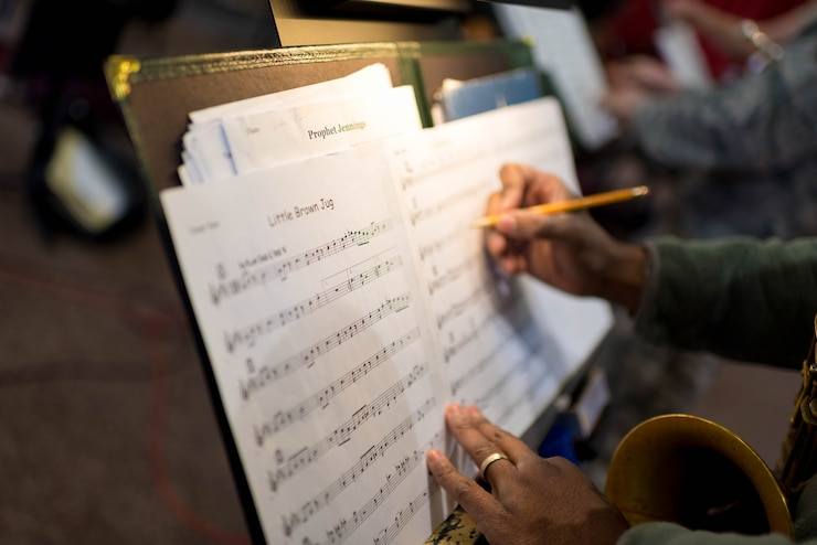 Image of a saxophone player making notes on sheet music during rehearsal