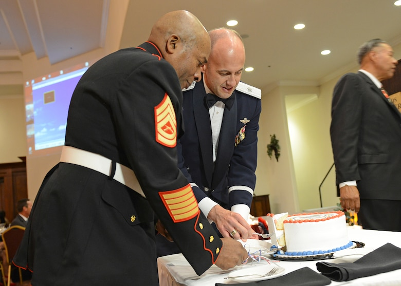 Brig. Gen. E. John Teichert, 412th Test Wing commander, cuts the ceremonial cake with retired Gunnery Sgt. James Baker at the Coffee4Vets Veterans Military Ball at the John P. Eliopulos Hellenic Center in Lancaster, California, Nov. 3. (U.S. Air Force photo by Kenji Thuloweit)