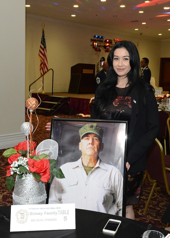 Betty Ermey, daughter of renowned actor and television personality R. Lee. Ermey, poses for a photo along with a picture of her late father at the Coffee4Vets Veterans Military Ball at the John P. Eliopulos Hellenic Center in Lancaster, California, Nov. 3. Betty Ermey spoke about her appreciation for military veterans at the event. (U.S. Air Force photo by Kenji Thuloweit)
