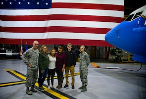 """First time enlistment welcomes new recruiter to 932nd Airlift Wing.   Patriotism...some wave a flag, some join the military, and some in many families support those who do both.  These moments in life are extra special when a person raises their right hand and agrees to """"support and defend the Constitution of the United States, against all enemies, foreign and domestic"""" and a family can come along for the historical moment.   Here, 932nd Airlift Wing Chief of Public Affairs, Lt. Col. Stan Paregien stands before the American flag immediately following the oath of enlistment for Chloe Mitchell, at center in white shirt, who enlisted into the United States Air Force Reserve at a ceremony on Scott Air Force Base, Illinois as members of her family witnessed.  The ceremony took place November 4, 2018, in the 932nd AW hangar one maintenance area next to a C-40 plane. The 932nd Career and Diversity Day was underway and the family then got a chance to walk around to various career booths.  The enlistment was facilitated by the background work of recruiter Staff Sgt. Jennifer Deimund, at far right.  This was her first finalized completed enlistment as a brand new recruiter.   """"It was really cool to see Chloe so motivated through the process.  It was fulfilling for me to work the recruiting process from cradle to grave and see a bright future and the beginning of Mitchell's career.  It involved constant contact, setting up calls and ASVAB tests, and physical.  I enjoyed seeing Chloe and her family's excitement,"""" said Deimund.   Sergeant Deimund is responsible for central Illinois and northeastern Missouri primarily.  For others interested in joining they can contact the recruiting office at (618)-910-1295 or (618)-229-7077 or toll free nationwide at 1-800-257-1212.  (U.S. Air Force photo by Senior Master Sgt. Melissa Melichar)"""