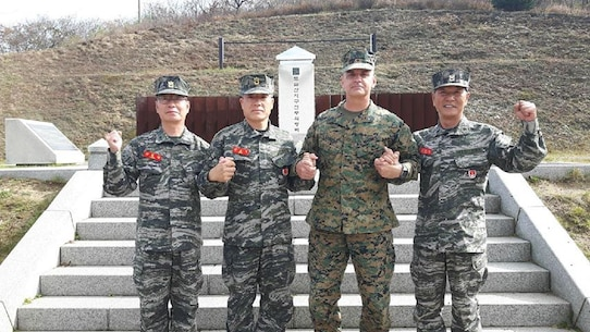 "DOSOL MOUNTAIN, Republic of Korea – Sgt. Maj. Michael Saucedo (center right), sergeant major of U.S. Marine Corps Forces Korea, with Sgt. Maj. Yang, Byung Jang (left), 1st R.O.K. Marine Division sergeant major, Sgt. Maj. Jeon, Jong Ik (center left), R.O.K. Marine Corps sergeant major, and Sgt. Maj. Lee, Hwai Woo (right), 2nd R.O.K. MARDIV sergeant major, hold hands in solidarity in front of the battle memorial of Dosol Mountain to symbolize the strength of our alliance here. Dosol Mountain is where U.S. and R.O.K. Marines who fought in the Korean War earned the nickname ""Mujuk"", which means invincible. The U.S. Marine Corps base in Pohang, South Korea was named Camp Mujuk to reflect this honor bestowed on them by the people of the R.O.K. (courtesy photo/Released)"