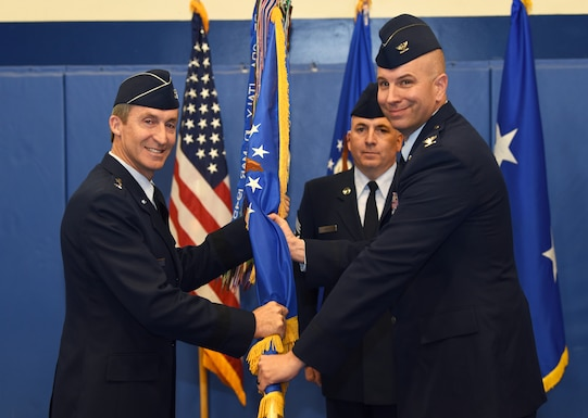 """Maj. Gen. Ronald """"Bruce"""" Miller, 10th Air Force commander, hands the 310th Space Wing guidon to Col. Dean D. Sniegowski, incoming 310th SW commander, during a change of command ceremony, Nov. 3rd, 2018."""