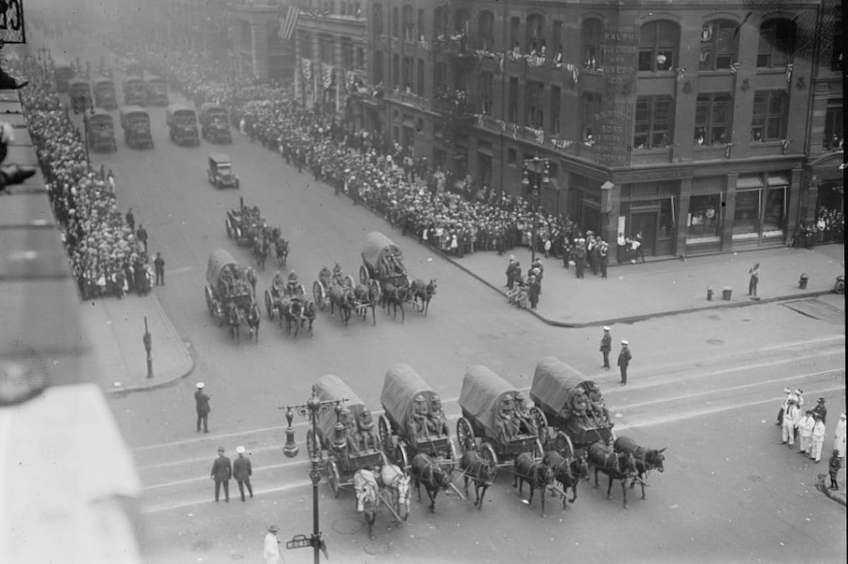 Horse-drawn carriages parade down a New York City street.