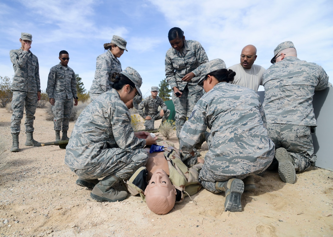 """Airmen from the 412th Medical Group provides care under fire for a """"victim"""" during a training exercise at Edwards Air Force Base, California, Nov. 1. The training ensures that Edwards medics are able to provide care in austere conditions. (U.S. Air Force photo by Giancarlo Casem)"""