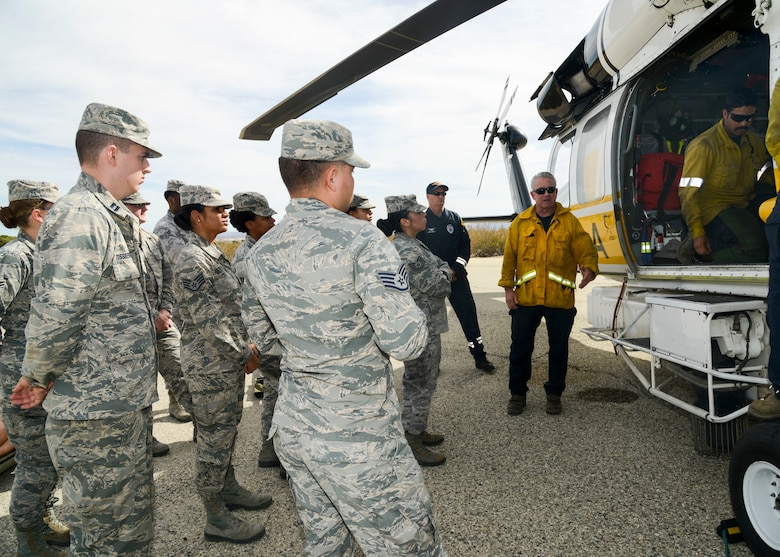 Members of a helicopter crew from the Los Angeles County Fire Department provide helicopter familiarization to Airmen from the 412th Medical Group during a training event at Edwards Air Force Base, California, Nov. 1. Interagency training allows the Airmen to be familiar with the helicopter, its crew and proper medevac standard operating procedures as Edwards AFB does not have native air medevac capabilities. (U.S. Air Force photo by Giancarlo Casem)