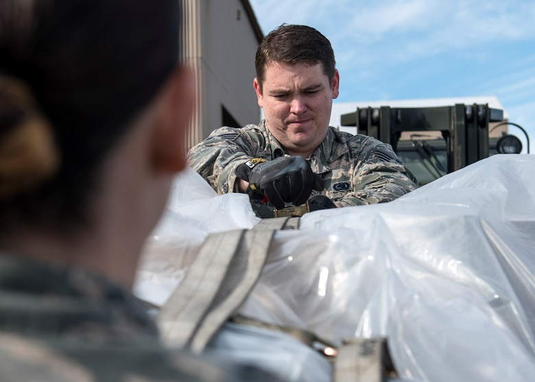 U.S. Air Force Staff Sgt. Justin Justice, 92nd Logistics Readiness Squadron journeyman, inspects and secures cargo to be loaded onto a KC-135 Stratotanker for transport at Fairchild Air Force Base, Washington, Oct. 17, 2018. From the moment boom operators receive a cargo request to load and secure items for transport, numerous Fairchild agencies contribute more than 30 working hours to support cargo loading mission completion. (U.S. Air Force photo/Airman 1st Class Whitney Laine)
