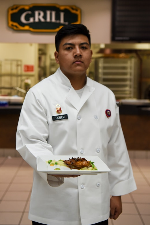 U.S. Army Pfc. Alejandro Gomez, a 2nd Battalion, 377th Parachute Field Artillery Regiment culinary specialist carries a dish to serve during the grand opening lunch for Joint Culinary Institute operated at the Gold Rush Inn. JCI is a new bi-monthly, two-week course, providing 10 food-service members from any military branch an opportunity to experience in-depth courses relating to the profession.