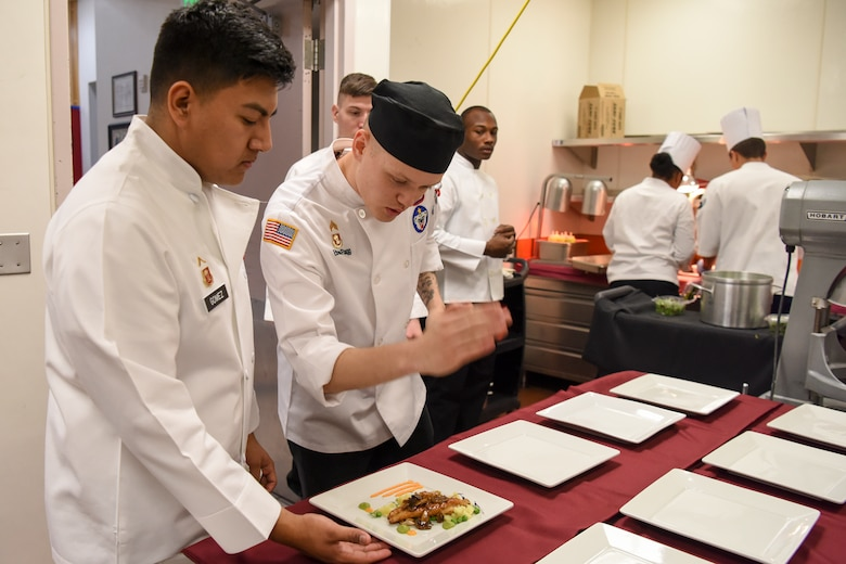 U.S. Army Sgt. Ethan Flagg, a 2nd Battalion, 377th Parachute Field Artillery Regiment culinary noncommissioned officer and Joint Culinary Institute instructor approves a dish for serving during the grand opening lunch for JCI operated at the Gold Rush Inn. JCI is a new bi-monthly, two-week course, providing 10 food-service members from any military branch an opportunity to experience in-depth courses relating to the profession.