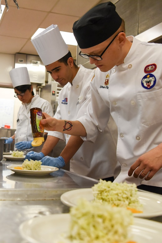 U.S. Army Sgt. Ethan Flagg, a 2nd Battalion, 377th Parachute Field Artillery Regiment culinary noncommissioned officer and Joint Culinary Institute instructor places honey on an orange tarragon salad during the grand opening lunch for JCI operated at the Gold Rush Inn. JCI is a new bi-monthly, two-week course, providing 10 food-service members from any military branch an opportunity to experience in-depth courses relating to the profession.