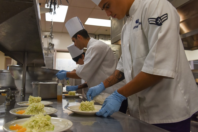 U.S. Air Force Airman 1st Class Jose Santana-Medina, 673d FSS food service specialist arranges salad placement for an orange tarragon salad being served during the grand opening lunch for JCI operated at the Gold Rush Inn. JCI is a new bi-monthly, two-week course, providing 10 food-service members from any military branch an opportunity to experience in-depth courses relating to the profession.