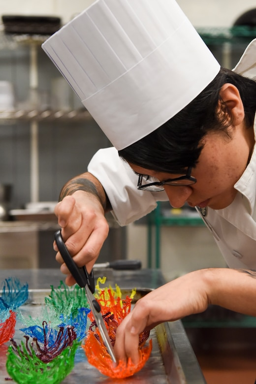 U.S. Army Spc. Abigail Hernandez, a 6th Brigade Engineer Battalion culinary specialist, prepares candy bowls during the grand opening lunch for the Joint Culinary Institute operated at the Gold Rush Inn. JCI is a new bi-monthly, two-week course, providing 10 food-service members from any military branch an opportunity to experience in-depth courses relating to the profession.