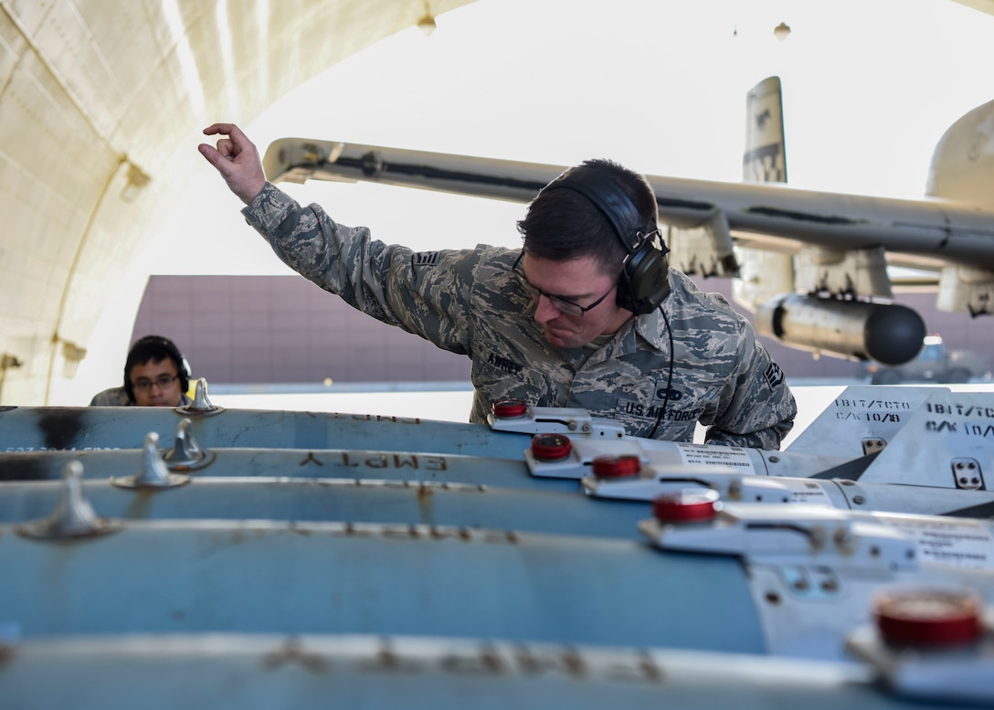 U.S. Air Force Staff Sgt. Nathaniel Awrey, 51st Maintenance Group standardized load crew team lead, signals U.S. Air Force Senior Airman Ryan Alquetra, 51st MXG standardized load crew team member, to lift munitions to load onto an aircraft at Osan Air Base, Republic of Korea, Nov. 2, 2018. The crew was able to load munitions onto the aircraft and send it off in under an hour by performing the loading operation while the aircraft engines were still running after hot refueling. (U.S. Air Force photo by Airman 1st Class Ilyana A. Escalona)