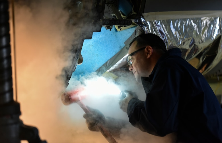 U.S. Air Force Staff Sgt. Joseph Gallegos, 309th Aircraft Maintenance Group depot structural maintenance specialist from Hill Air Force Base, Utah, attempts to remove the bulkhead of an F-16 Fighting Falcon with liquid nitrogen at Kunsan Air Base, Republic of Korea, Nov. 8, 2018. Replacement parts are being installed to change dated parts on F-16s in the Wolf Pack fleet and to sharpen the 8 Fighter Wing's lethality. (U.S. Air Force photo by Senior Airman Stefan Alvarez)