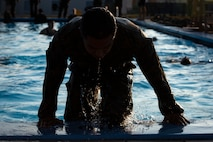 A U.S. Marine with Headquarters and Support Battalion, Marine Corps Installations Pacific, climbs out of a pool during Marine Corps Water Survival Training on Camp Foster, Okinawa, Japan, Nov. 7, 2018. The training requires Marines to employ water survival skills to reduce fear, raise self-confidence, and develop the ability to survive in aquatic environments.