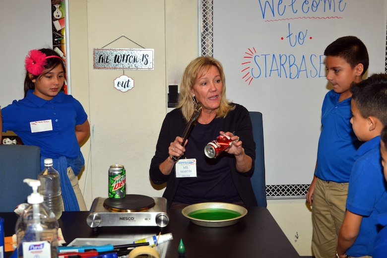 Kathy Martin, Starbase Kelly director, uses soda cans to demonstrate air pressure properties to Mildred Baskin Elementary students at Joint Base San Antonio-Lackland, Texas Nov. 5, 2018.