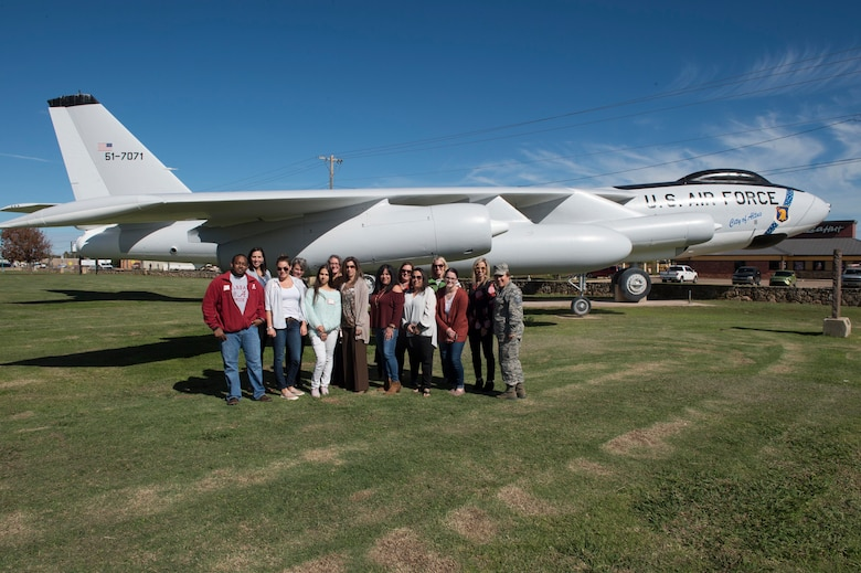 Military spouses from the 97th Air Mobility Wing and members of the 97th Force Support Squadron Airman and Family Readiness Center pose in front of a static B-47 Stratojet display during the Heartlink Spouse Orientation
