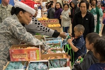Alaska Air National Guard Staff Sgt. Vanessa Peterson hands out snacks to children in Emmonak during Operation Santa Claus on Nov. 1, 2018. Operation Santa Claus is an Alaska National Guard annual community outreach program that provides Christmas gifts, books, backpacks filled with school supplies, fresh fruit, and sundaes to youngsters in rural communities.