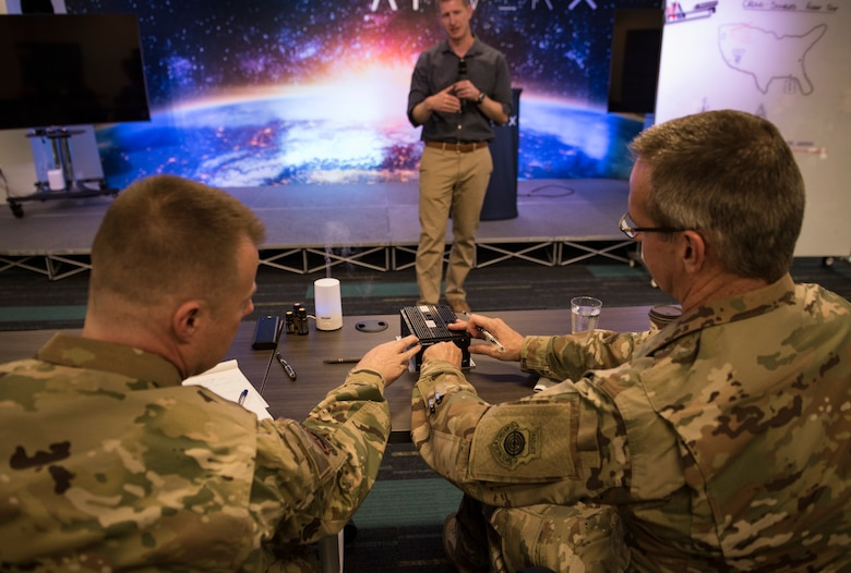 Lt. Col. Justin Elliott, 59th Test and Evaluation Squadron director of operations, presents his idea to Maj. Gen. Peter Gersten, U.S. Air Force Warfare Center commander, and Chief Master Sgt. Charles Hoffman, USAFWC command chief, at AFWERX-Vegas, Oct. 29, 2018. Elliot was one of the two presentations that was selected to advance to present in front of Air Combat Command. (U.S. Air Force photo by Airman 1st Class Andrew D. Sarver)