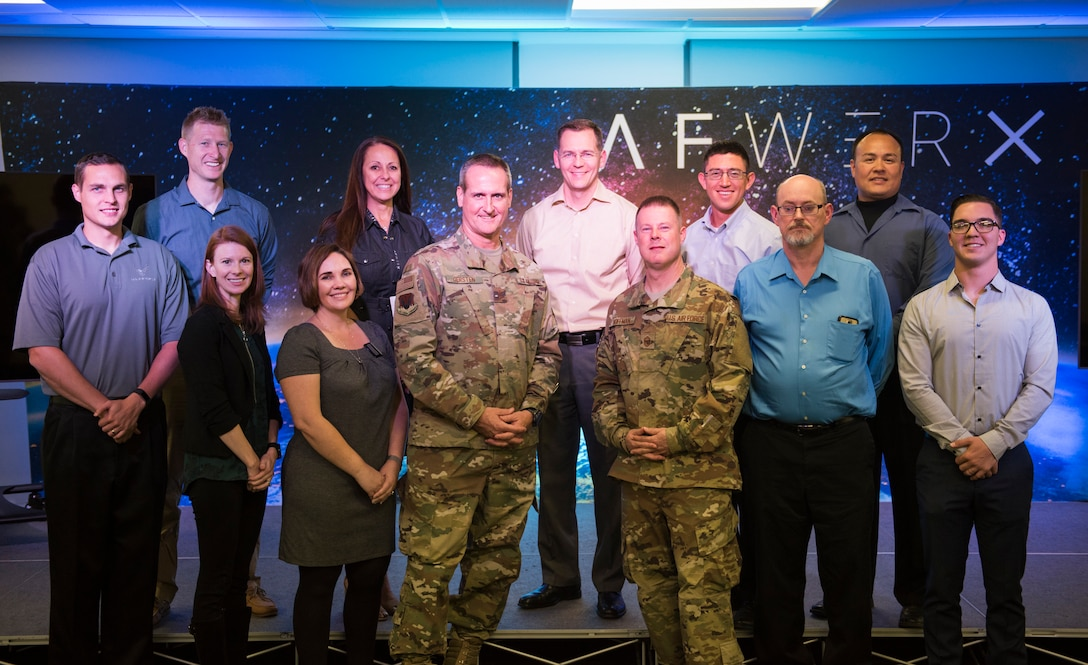 Maj. Gen. Peter Gersten, U.S. Air Force Warfare Center commander, and Chief Master Sgt. Charles Hoffman, USAFWC command chief, stand with members of the Spark Tank prelims at AFWERX-Vegas, Oct. 29, 2018. Seven members presented their ideas to Gersten and Hoffman. Two were selected to move on to present at the Air Combat Command level.