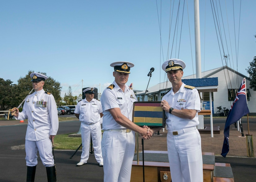 Chief of Naval Operations Adm. John M. Richardson and an Australian sailor hold a framed striped pennant.