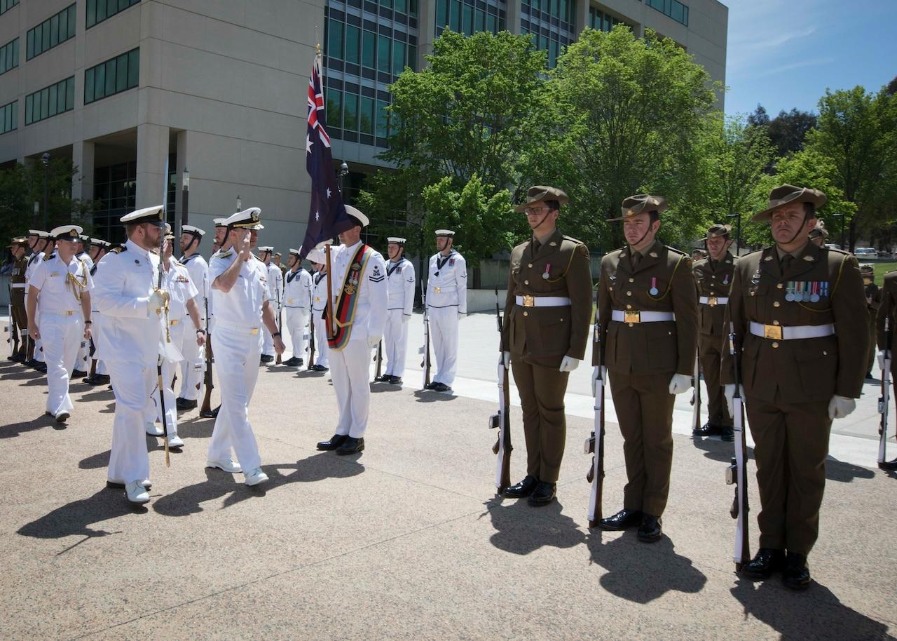 Chief of Naval Operations Adm. John M. Richardson salutes Australian honor guard troops.