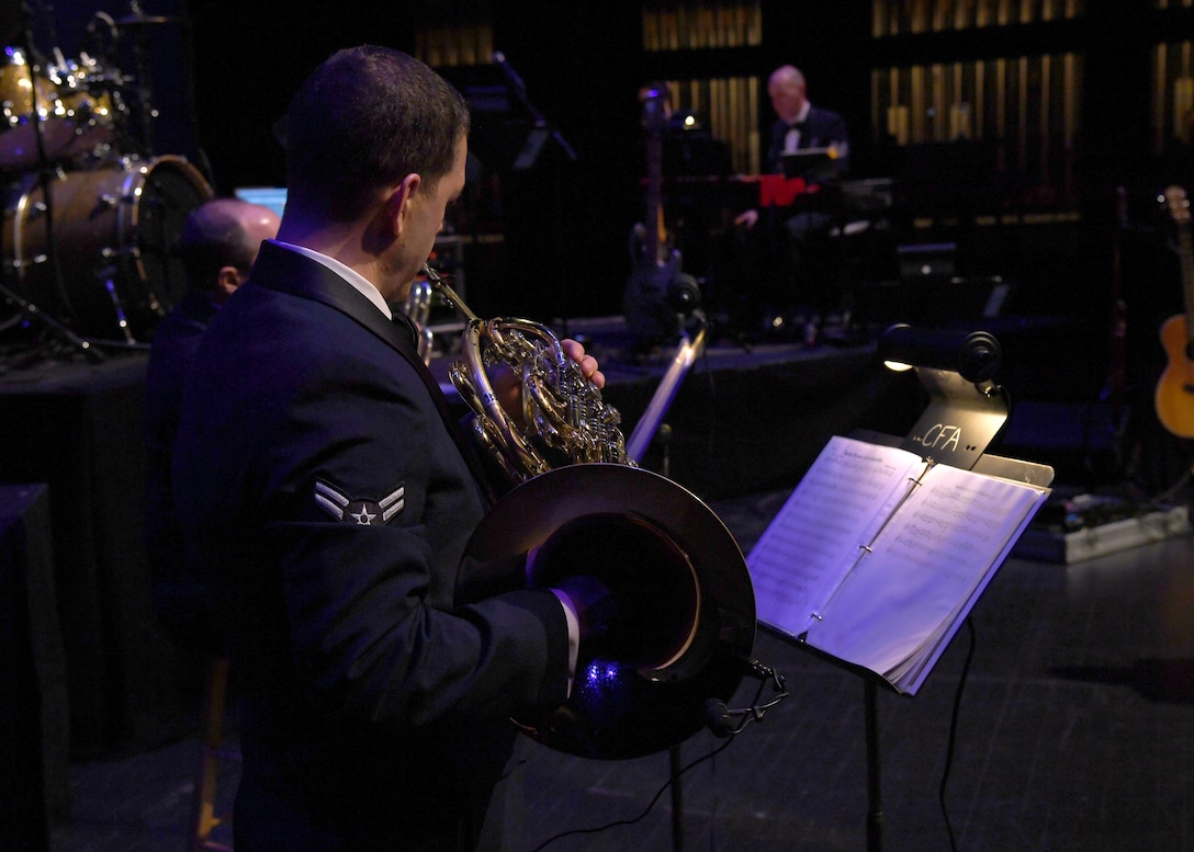 "Airman 1st Class Jon Anderson, U.S. Air Force Heartland of America Band French horn player, follows a score as he plays his instrument during a concert at the Chester Fritz Auditorium November 6, 2018, in Grand Forks, North Dakota. The concert was a special veterans Day performance which included a variety of tributes and American classics to include ""Amazing Grace,"" ""America the Beautiful,"" and ""God Bless America."" (U.S. Air Force photo by Airman 1st Class Elora J. Martinez)"
