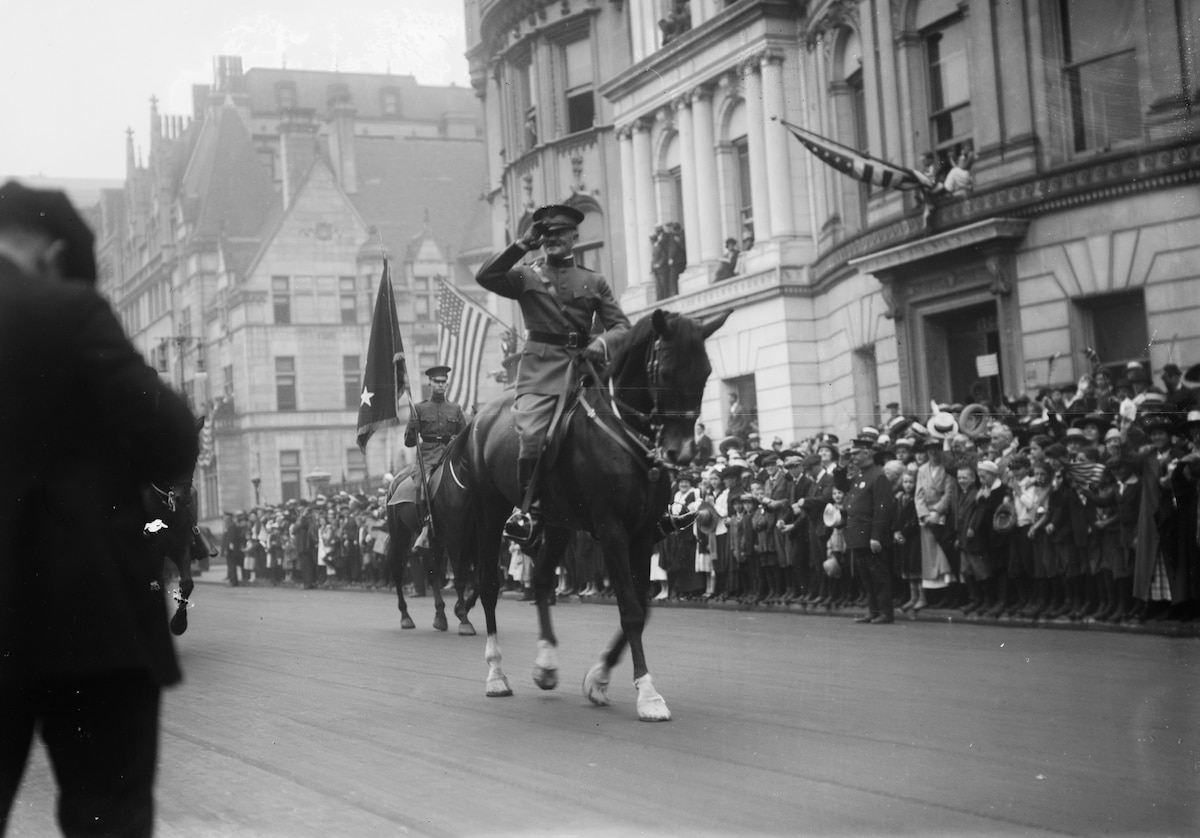 Army Gen. John J. Pershing salutes while parading on horseback on a city street filled with onlookers.